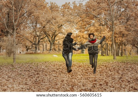 Young women running in the park over a field full of leaves. Autumn landscape