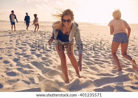 Young women running race on the beach. Group of young people playing games on sandy beach on a summer day. Having fun on the beach. - stock photo