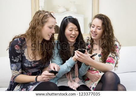 Young women sharing video on cell phone - stock photo