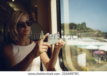 young women shooting landscape in a moving train  - stock photo