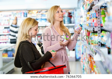 Young women shopping together in the supermarket with people in the background - stock photo
