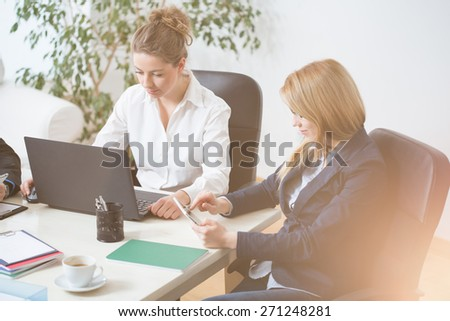Young women sitting and working in office - stock photo