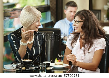 Young women sitting at table in cafe, drinking coffee eating cake, talking.