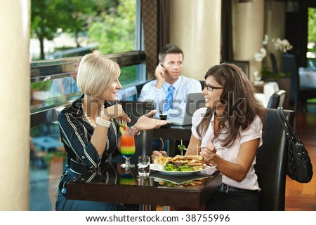 Young women sitting at table in cafe, eating sandwich and drinking cocktail, talking.