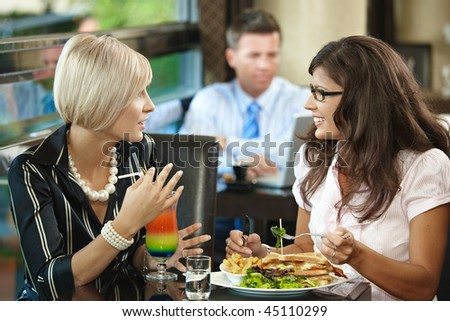 Young women sitting at table in cafe, eating sandwich and drinking cocktail, talking. - stock photo