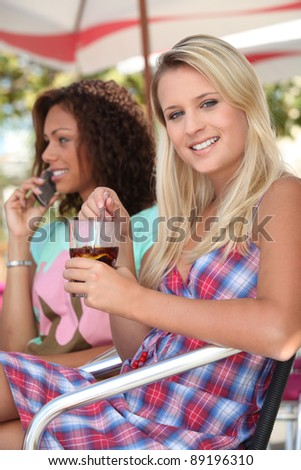 Young women sitting in a cafe - stock photo