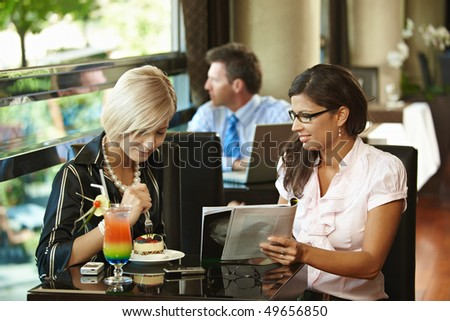 Young women sitting in cafe having sweets, looking at magazine. - stock photo