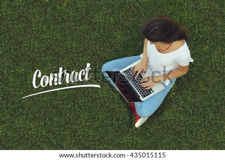 Young women sitting on the grass on a Tablet PC is searching for Contract. - stock photo