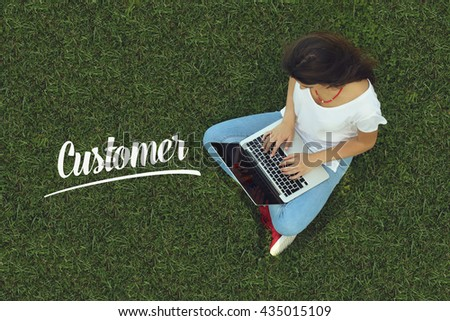 Young women sitting on the grass on a Tablet PC is searching for Customer. - stock photo