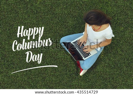 Young women sitting on the grass on a Tablet PC is searching for Happy Columbus Day. - stock photo
