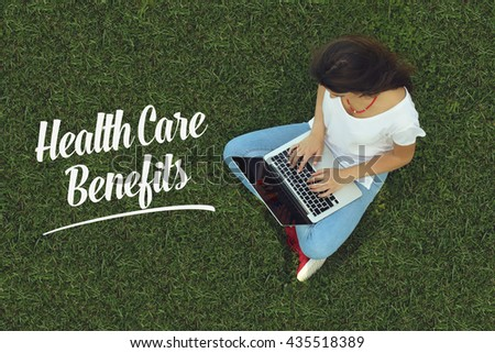 Young women sitting on the grass on a Tablet PC is searching for Health Care Benefits . - stock photo