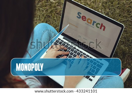 Young women sitting on the grass on a Tablet PC is searching for Monopoly.