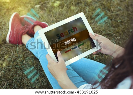 Young women sitting on the grass on a Tablet PC is searching for Right Way. - stock photo