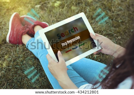 Young women sitting on the grass on a Tablet PC is searching for Stop Depression. - stock photo