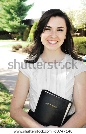 Young women smiling while holding a Bible/Young Woman Holding a Bible - stock photo