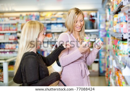 Young women smiling while shopping together in the supermarket - stock photo