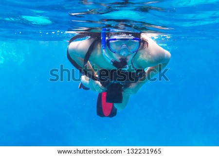 Young women snorkeling in the Andaman sea with underwater camera - stock photo