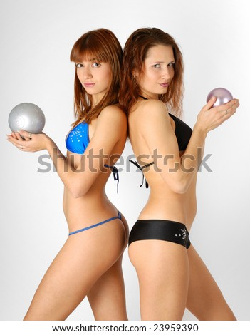 Young women snuggles back together and holds ball in hands