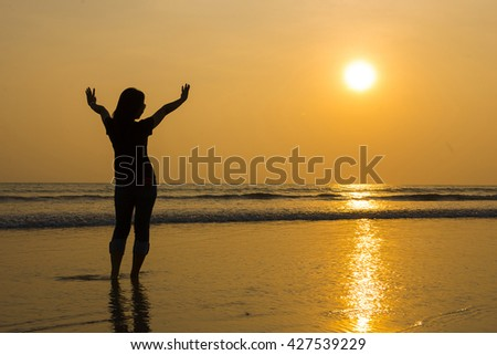 young women standing on sandy at the beach, sunset time - stock photo