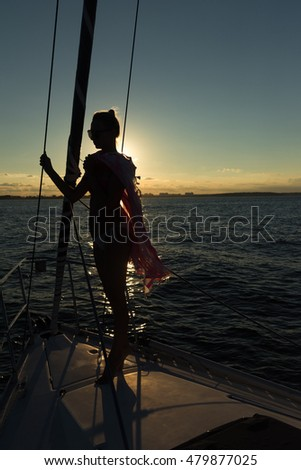 Young women standing on the edge of the sailboat at time of sunset