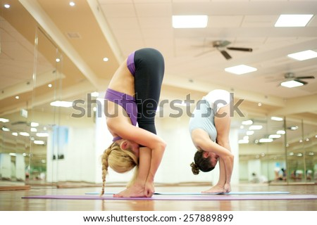 Young women stretching their leg muscles, touching their knees with noses - stock photo