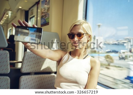 young women take a selfie in a moving train against the train window with the seascape - stock photo