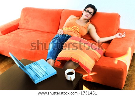 Young women takes a break and sleeps on the couch. - stock photo