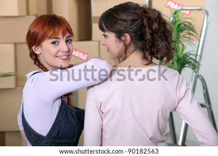 Young women taking a break on moving day - stock photo