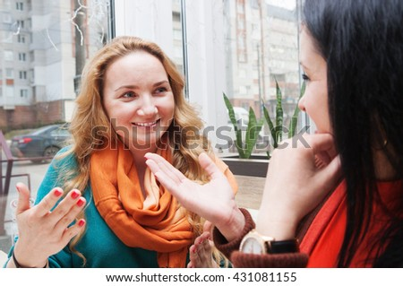 Young women talking and drinking coffee in a small cafe