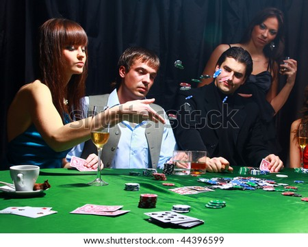 Young women throwing chips on the table while playing cards - stock photo