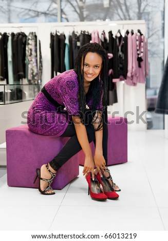 Young women trying on new jogging shoes on the shop - stock photo