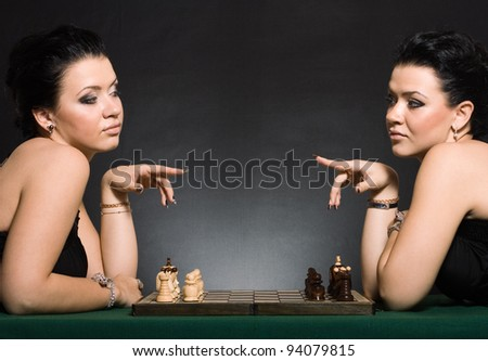 Young women twins play chess. The idea of competition. - stock photo