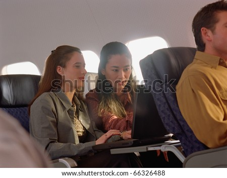 Young women using laptop on airplane - stock photo