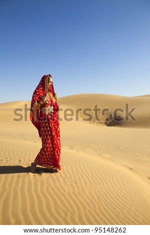Young women wearing a saree on the dunes of the Thar Desert, Rajasthan - India - stock photo