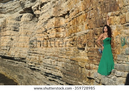 young women wearing green dress and posing on the rocks - stock photo