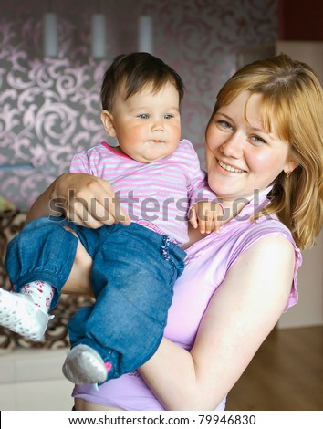 Young women with a little child at home. Shallow DOF, focus on baby - stock photo