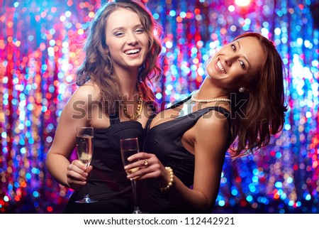 Young women with champagne enjoying themselves at club