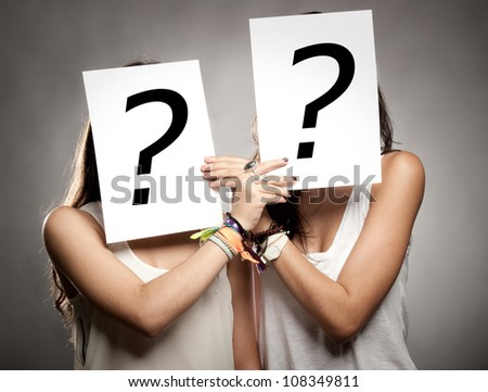 young women with interrogation symbols in front of their faces - stock photo