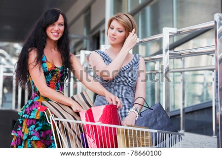 Young women with shopping cart - stock photo