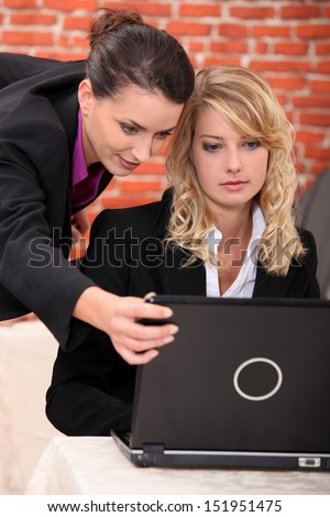 Young women working at a laptop - stock photo