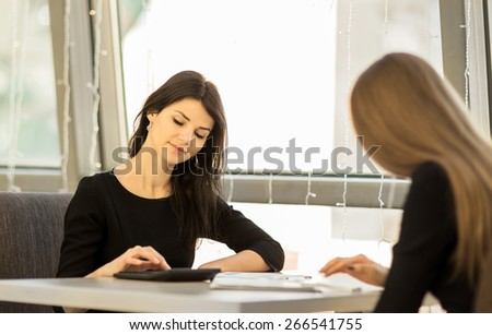 Young women working in the office, sitting at a table, using a calculator, smiling, colleagues