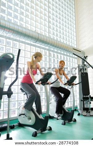 Young women working out  on bike at gym. - stock photo