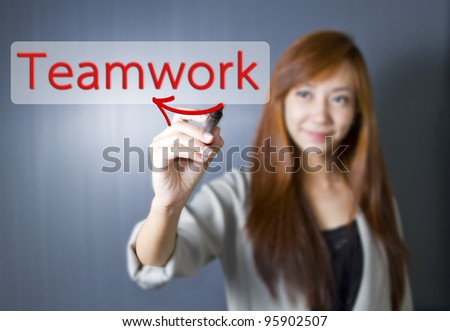 Young women write Teamwork word. - stock photo