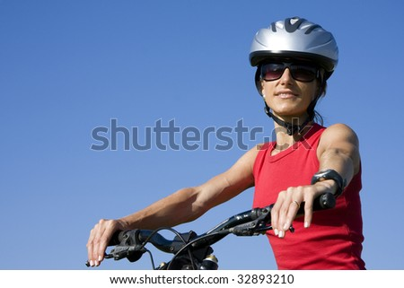 Young womnem with helmet cycling isolated on blue sky