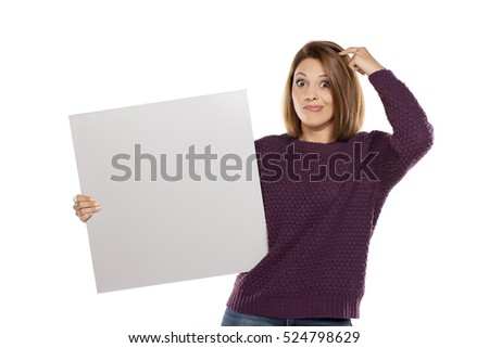 young wondering woman in a purple sweater and jeans, holding a blank board for advertising