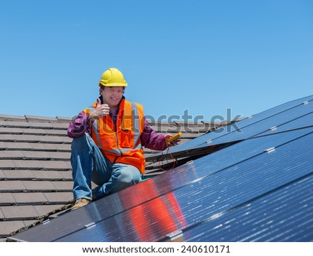 young worker checking solar panels on house roof - stock photo