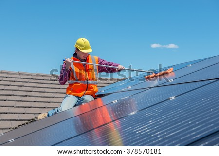 young worker cleaning solar panels on house roof
