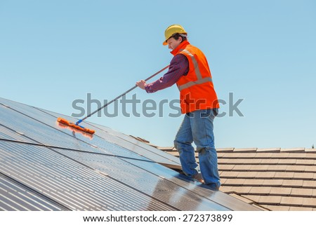 Young worker cleaning solar panels on the roof.Focus on the worker. - stock photo