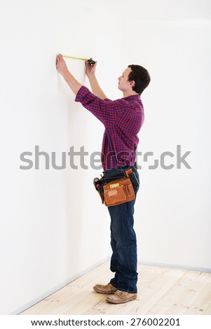 Young worker handyman with measuring tape near the wall in room  - stock photo