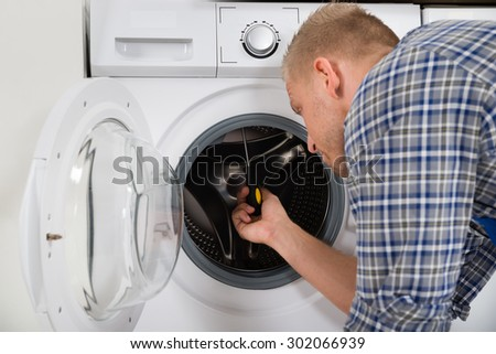 Young Worker In Overall Fixing Washing Machine In House